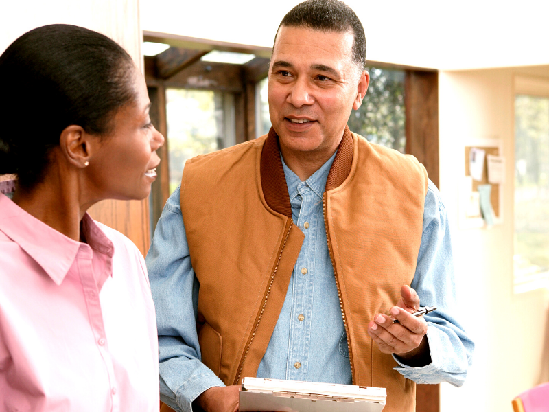 A man and a woman go over a home inspection report.