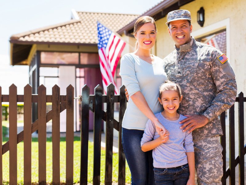 A man in his military uniform, a woman, and their child stand in front of their house.