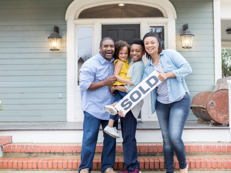 A family stands outside their newly-purchased home.