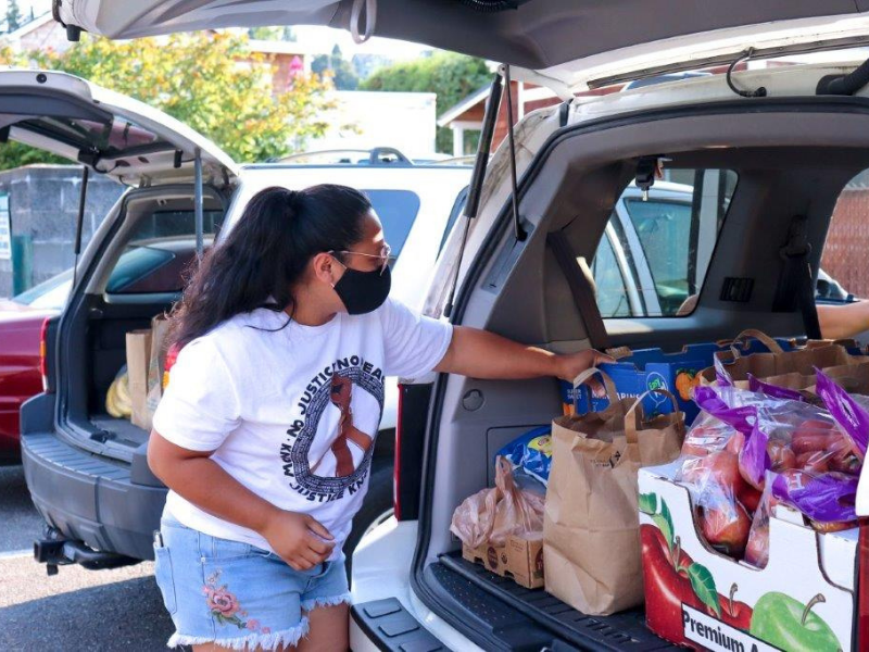 A woman unpacks food donations from the back of a vehicle.