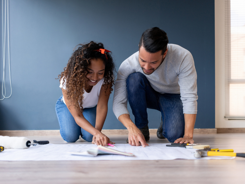 A man and a woman look at their home renovation blueprints.