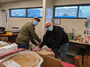 Two men unpack a box of food donations for a Thanksgiving meal.