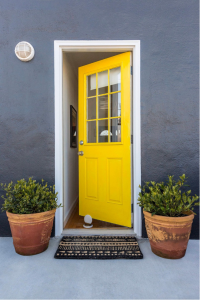 A yellow front door against a gray wall.