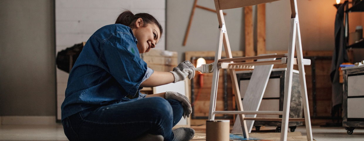 A woman restores a chair in a craft room.