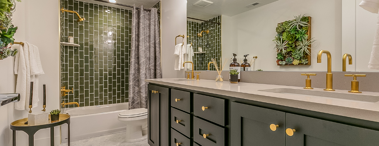 A bathroom with dark green cabinets, green shower tiles, and gold fixtures.