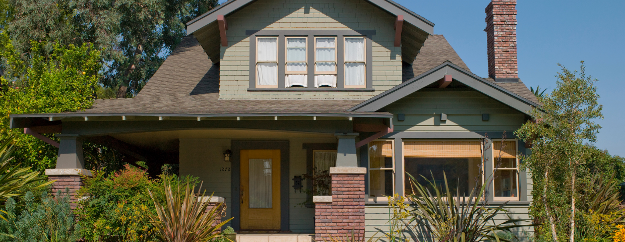 A green craftsman home with a large porch.