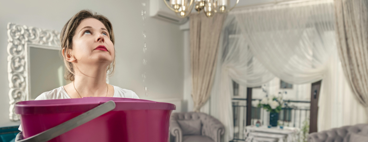 A woman stands in her living room holding a bucket to catch a ceiling leak.