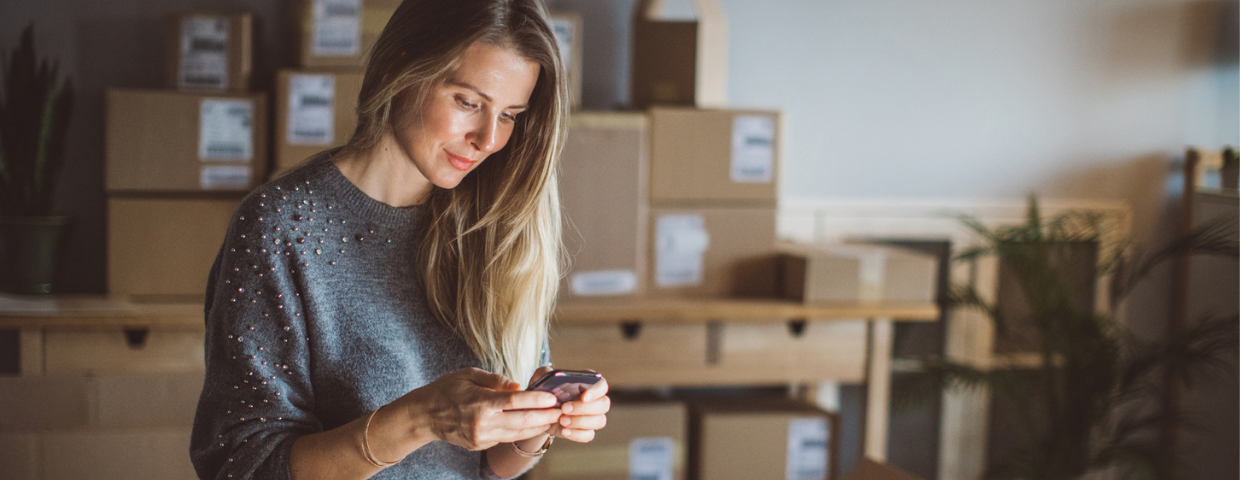 A woman surrounded by boxes in her home checks her phone.