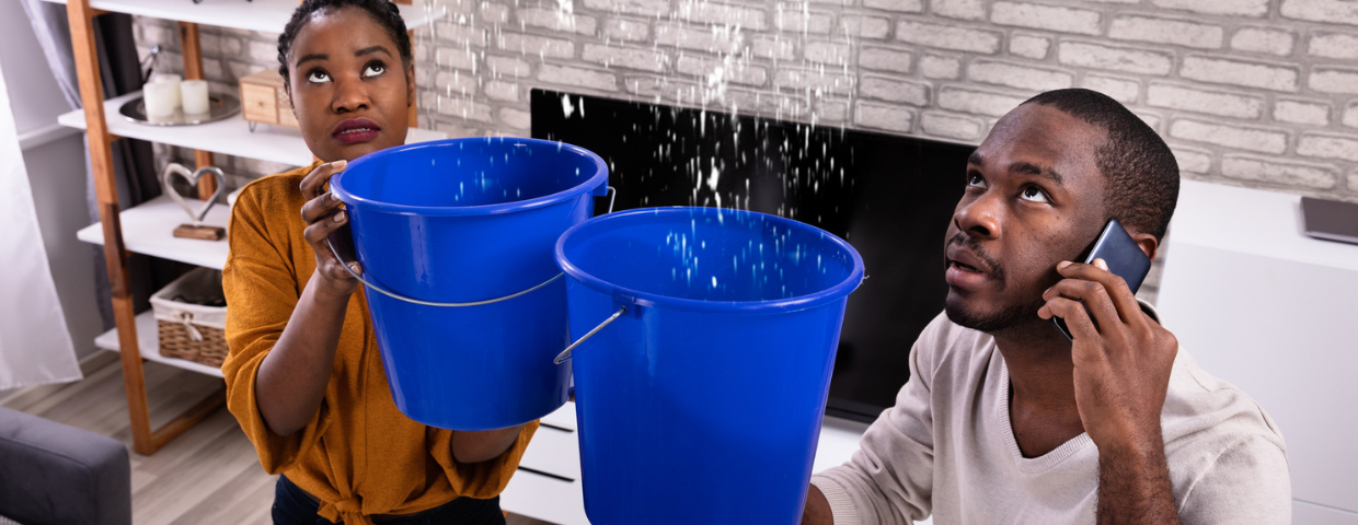 A man and a woman hold buckets catching water dripping from the ceiling.