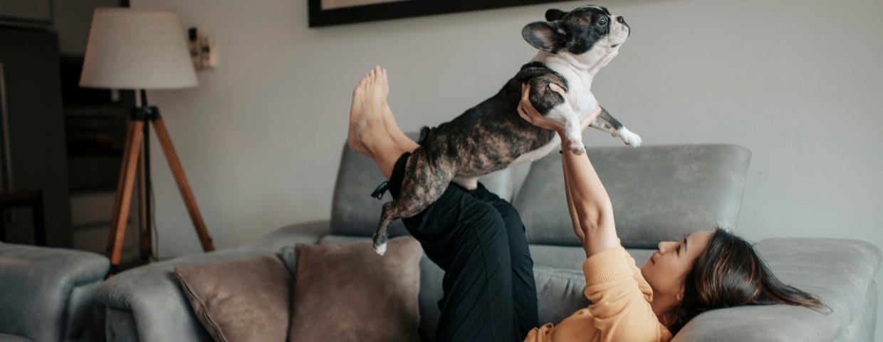 A woman lifts her dog in the air while sitting on the couch.