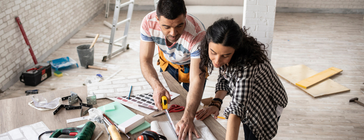 A man and woman take measurements on a table as they renovate their home.