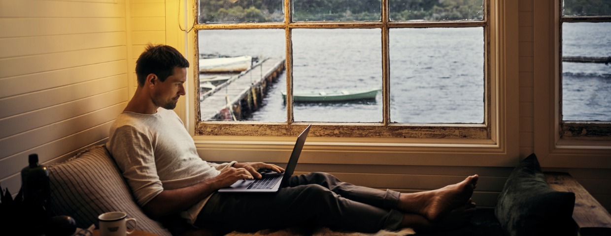 A man works on his laptop with a view of a lake outside the window.