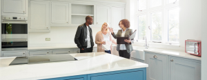A real estate agent shows a kitchen to a man and a woman.
