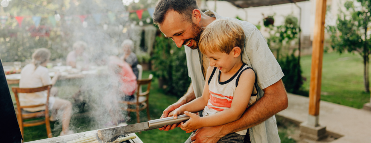 A man and a child turn corn on the barbecue in their backyard.