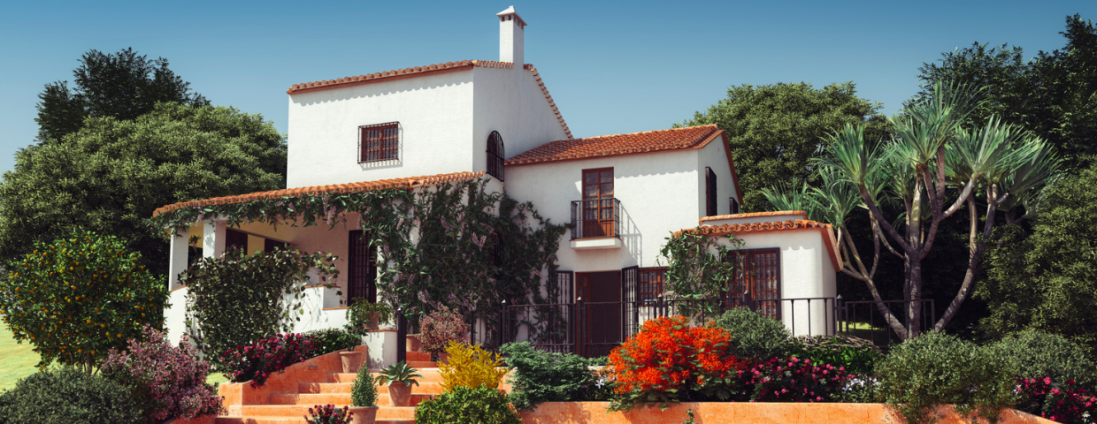 A Mediterranean-style vacation home surrounded by flowers and trees.
