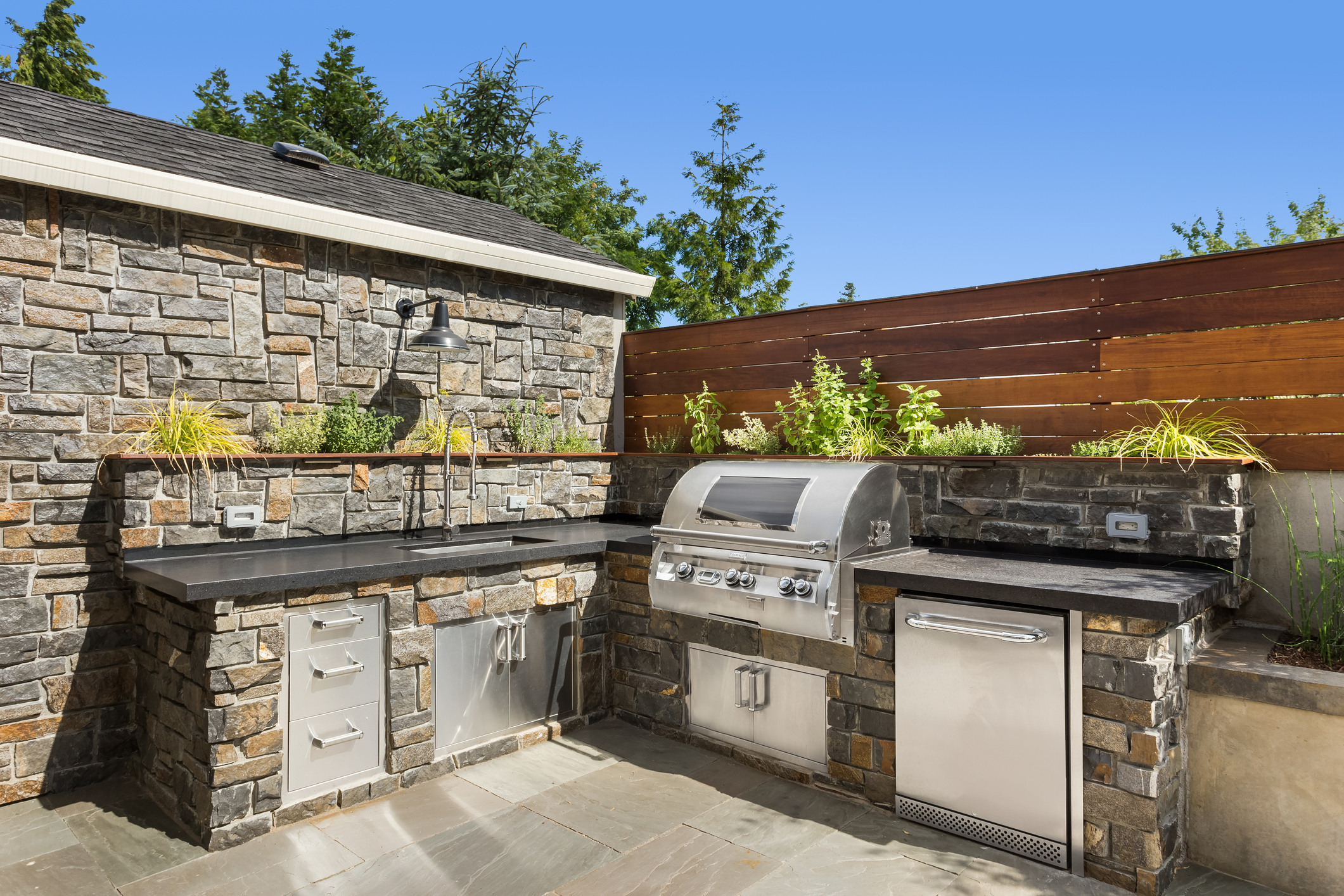 An outdoor kitchen with a sink, barbecue, and dishwasher.