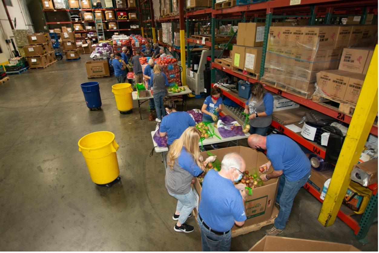 A group of people bag produce in a warehouse.