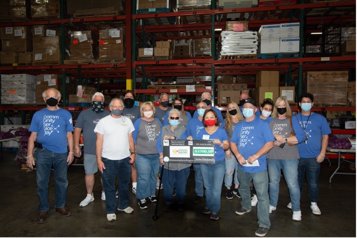 A group of people hold up a check in a warehouse.