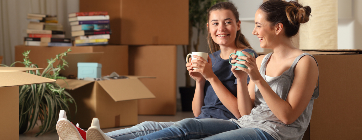 Two young women sit in their new home surrounded by boxes.