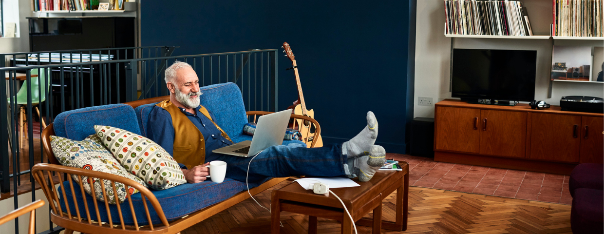 A happy senior man sits in his home decorated with vintage items.