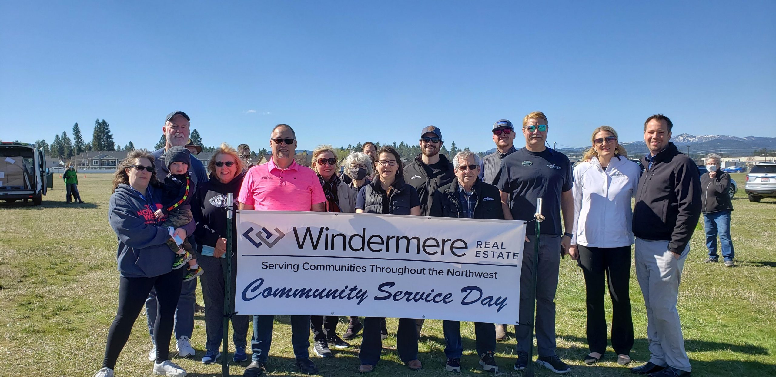 A group of people hold a Windermere Community Service Day banner.