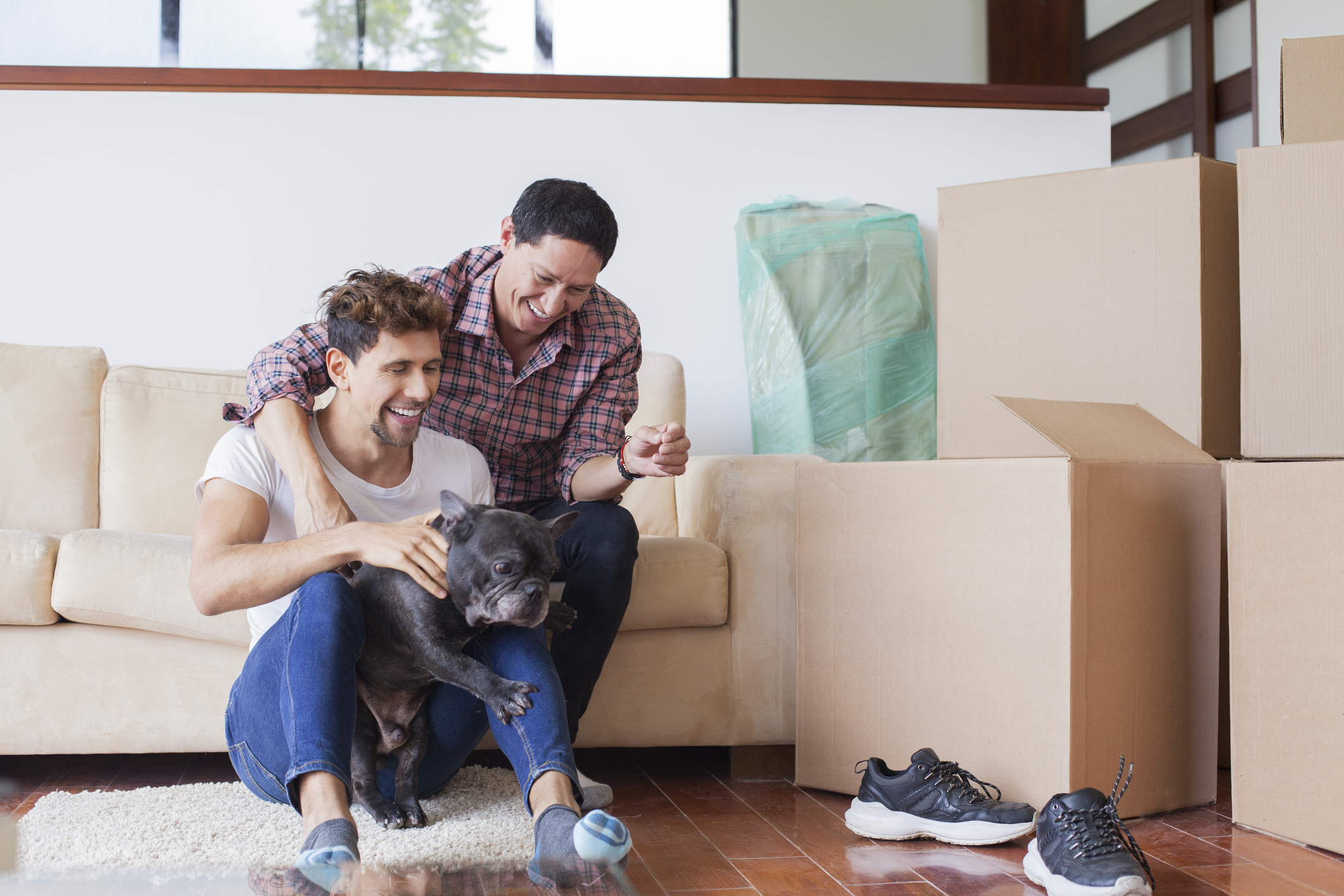 Two men and their dog move into a new home.