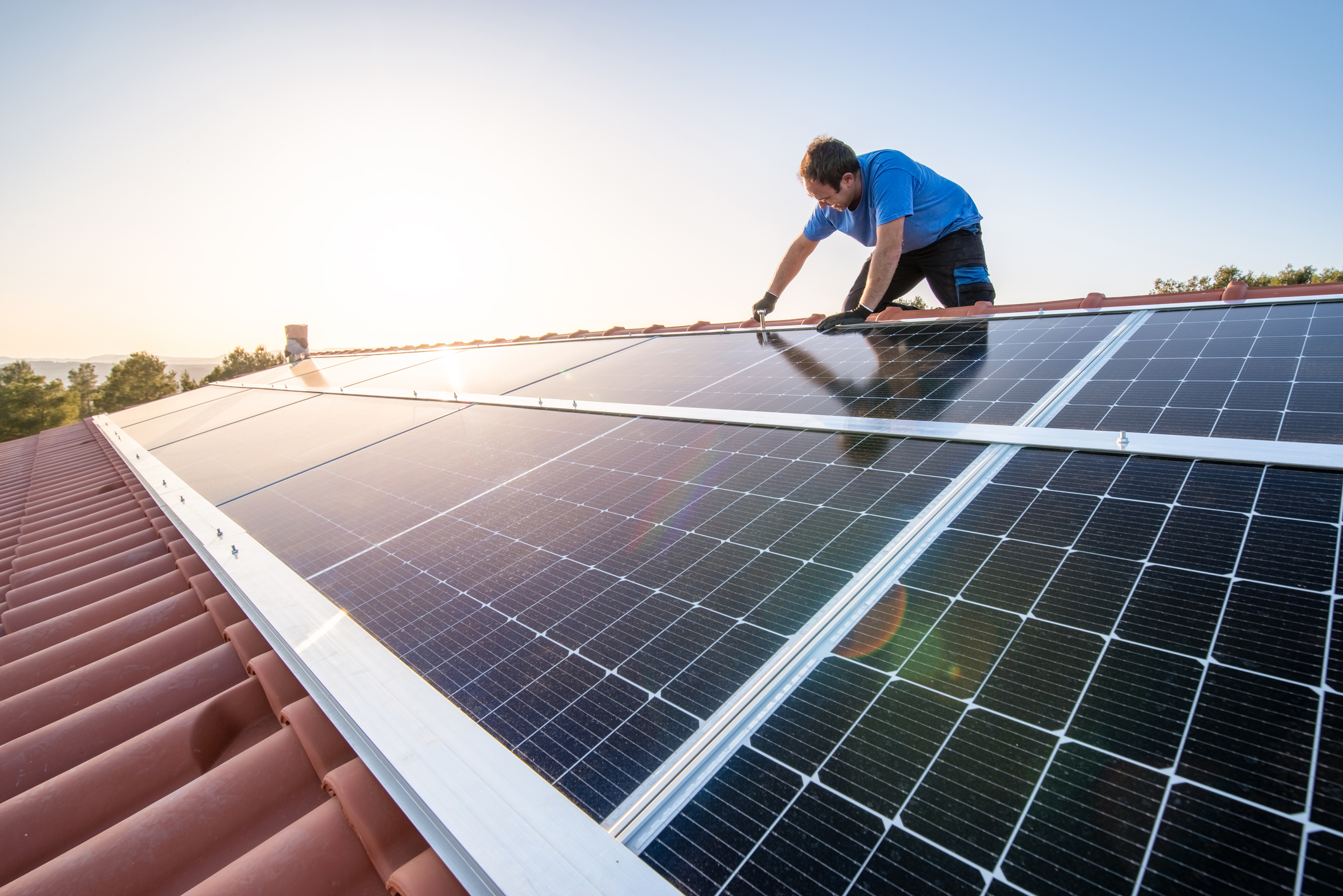 A man installs solar panels on the roof of a house.