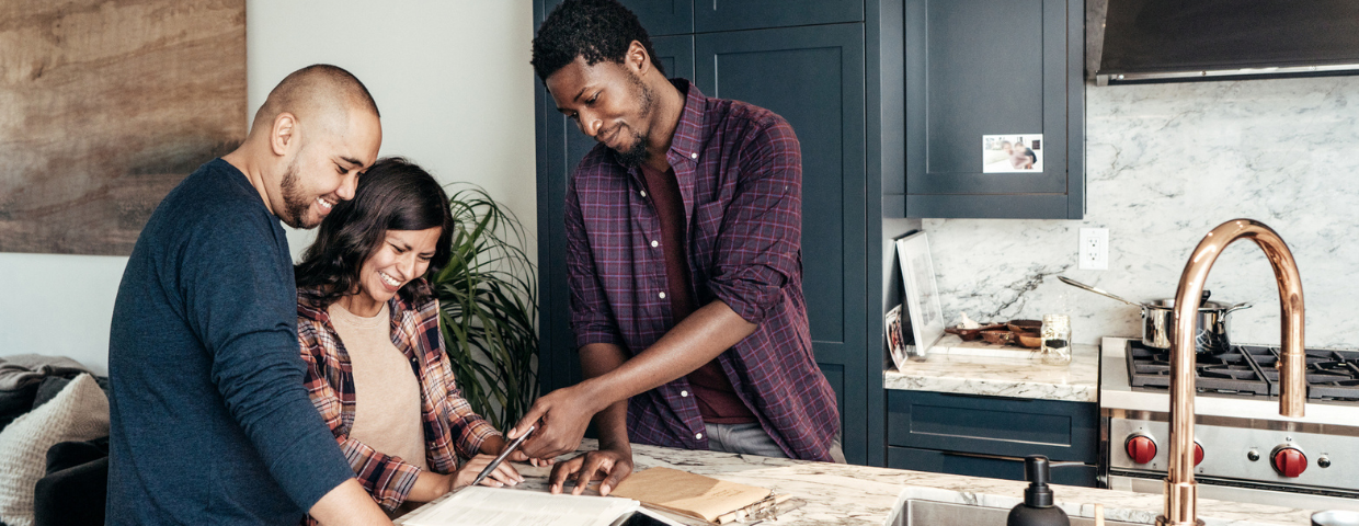 A real estate agent goes through paperwork with a man and a woman.