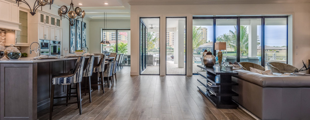 A modern home with wood flooring covering its open kitchen and living room area.