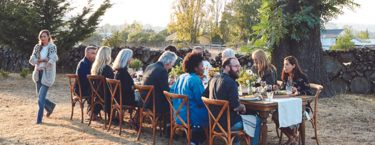 A group of people sit around a large table at a backyard party.