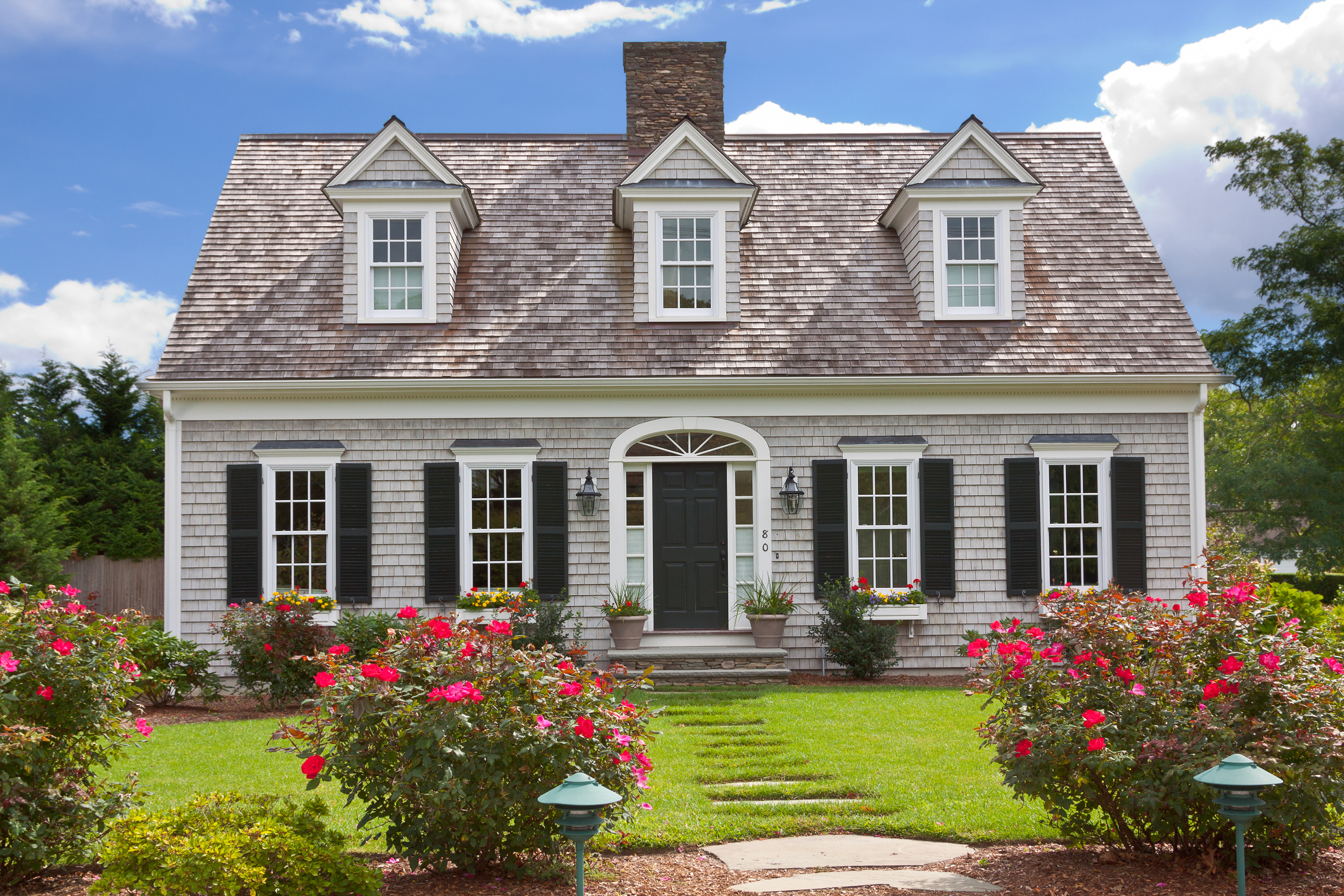 A close-up of the exterior of a cape cod home.