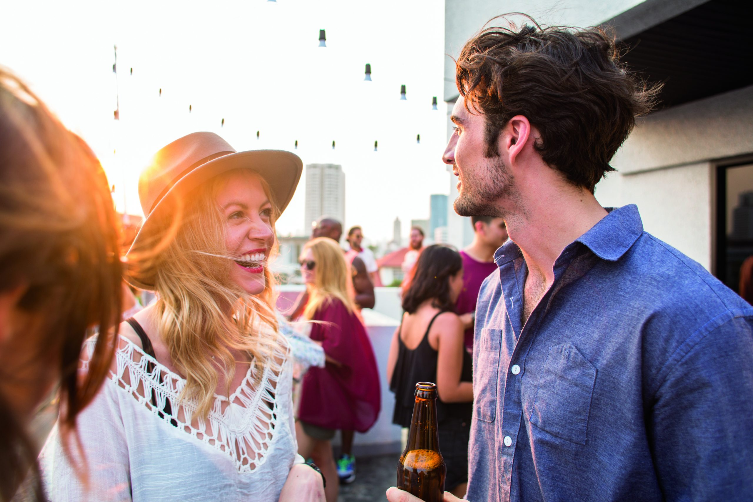 A man and a woman attend an outdoor party during sunset.