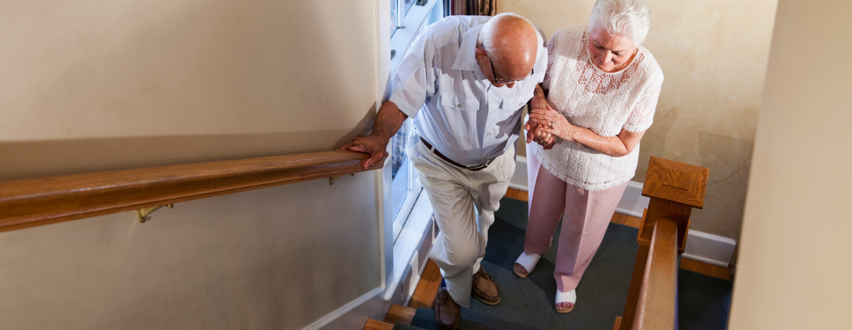 An elderly couple climbs the stairs in their home.