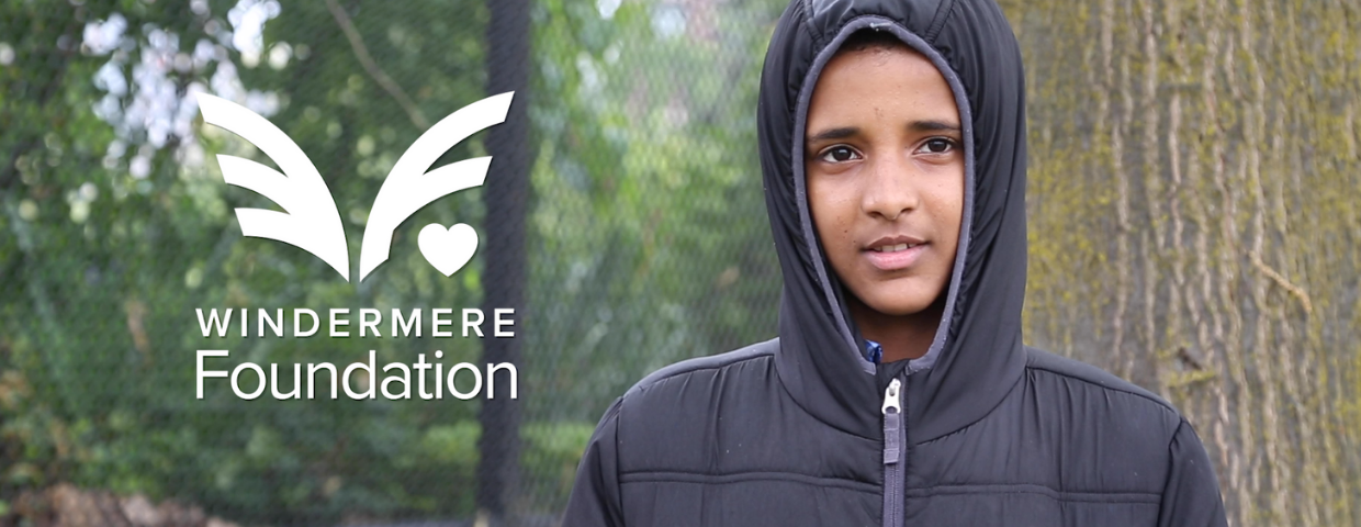 A young boy in a hood with the Windermere Foundation logo superimposed next to him.