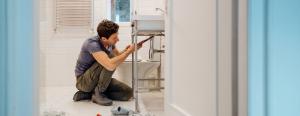A man repairs the plumbing in his bathroom.