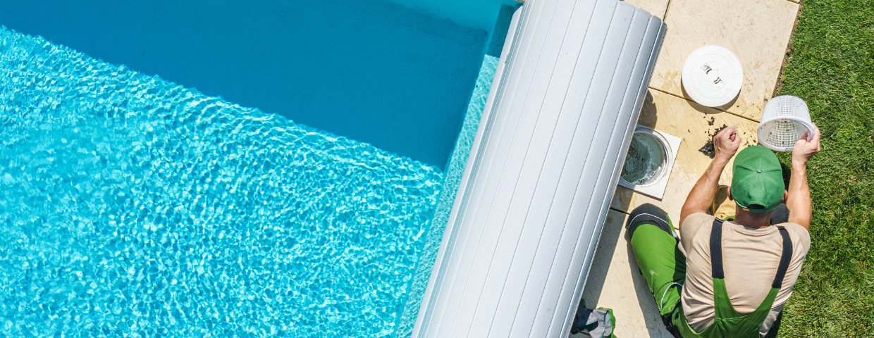 A man cleans a swimming pool on a sunny day.