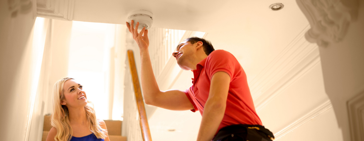 A man and a woman examine a smoke detector in their home.