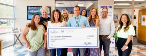 A group of people inside a school hold up a check for one-thousand dollars.