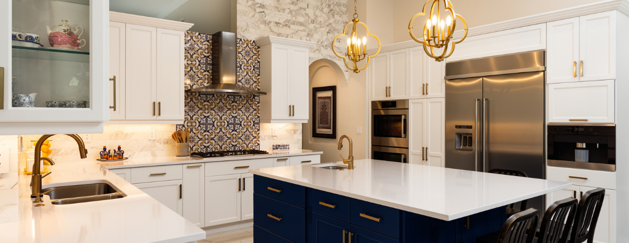 A kitchen with white surfaces, decorative tile, a blue island, and gold light fixtures.
