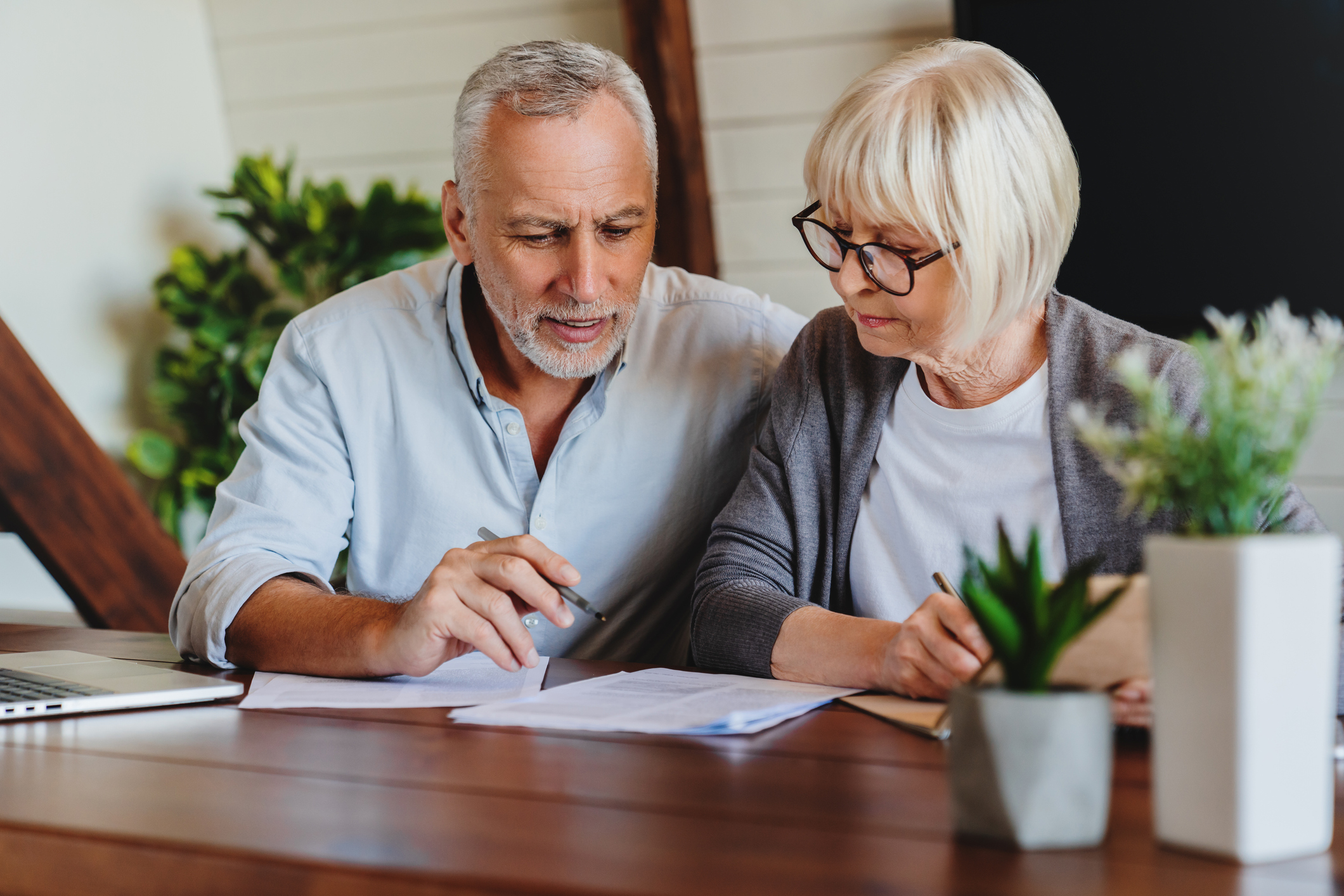 An older man and woman examine financial paperwork at their dinner table.