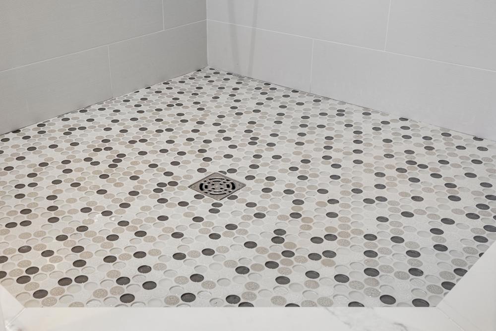 Ett duschgolv av neutralfärgade öreplattor.