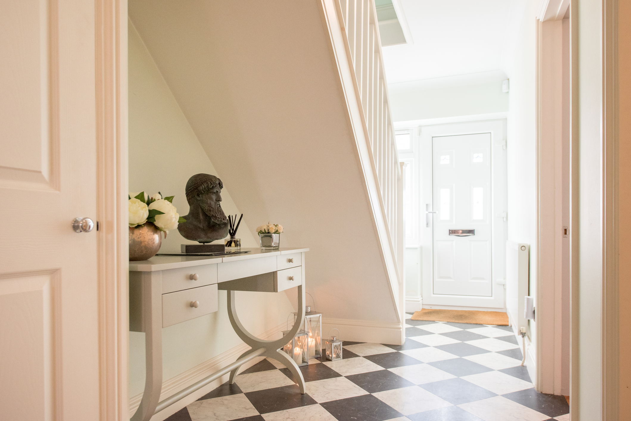 En hall i ett hus med ett rutmönster och ett skrivbord under trappan.