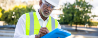 A home inspector wearing a hard hat fills out paperwork on his clipboard.
