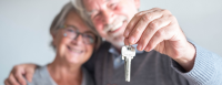 An elderly man and woman hold the keys to their new home.